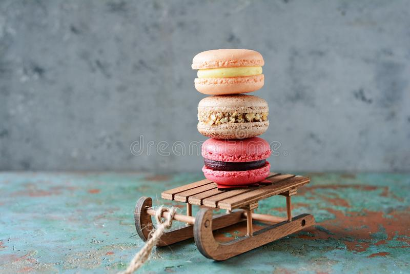 Stack of sweet french macarons cake on a decorative sled on blue background. Top view, copy space for text. Small French desert. royalty free stock image