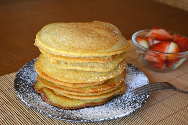 Stack of sweet pancakes with fresh strawberries and icing sugar royalty free stock photography