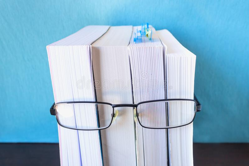 A stack of thick new books and black glasses depict a person`s face. Concept- reading, preparation for exams, training. Selective focus royalty free stock photography