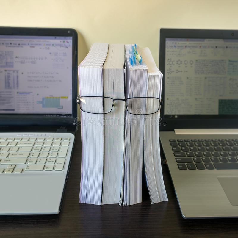 A stack of thick new books and black glasses depict a person`s face. Concept- reading, preparation for exams, training. Selective focus royalty free stock photos