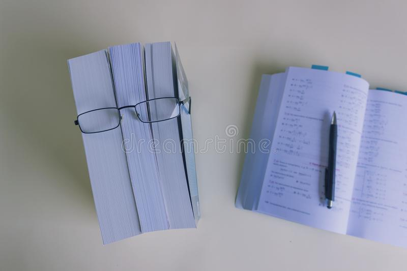 A stack of thick new books and black glasses depict a person`s face. Concept- reading, preparation for exams, training. Selective focus royalty free stock image