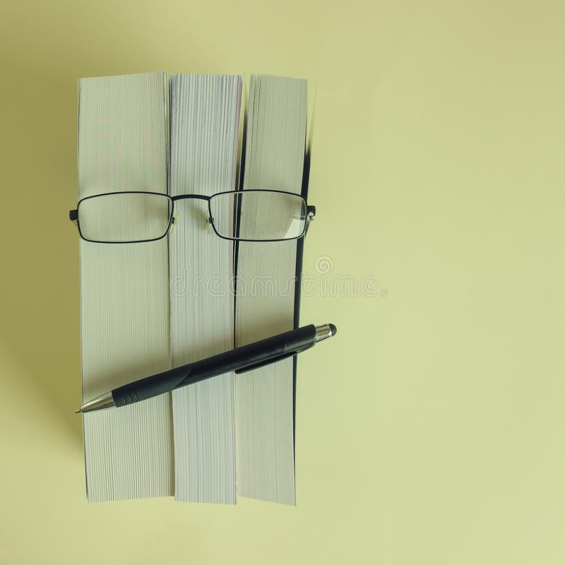 A stack of thick new books, glasses and a pencil depict a person`s face. Concept- reading, preparation for exams, training. Selective focus stock photos