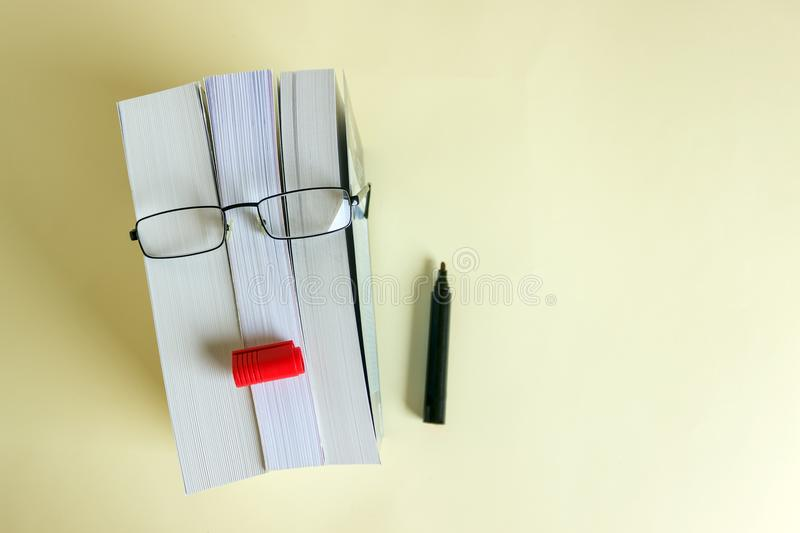 A stack of thick new books, glasses and a pencil depict a person`s face. Concept- reading, preparation for exams, training. Selective focus stock photo
