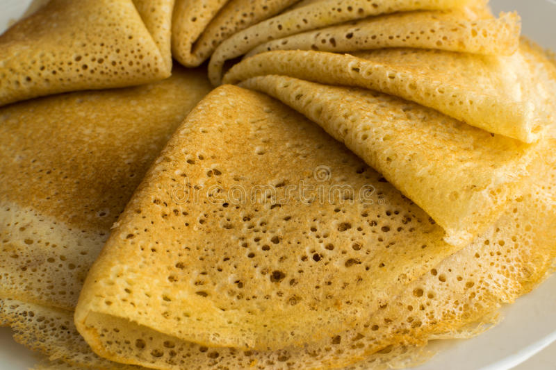 Stack of Thin Pancakes or Crepes. Stack of Thin Pancakes on a White Plate. Fresh Homemade Porous Crepes royalty free stock photos