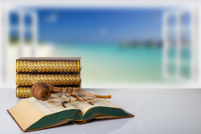 A stack of three books and an opened old book with a pair of glasses and a tobacco pipe on them in front of bright blurred stock images