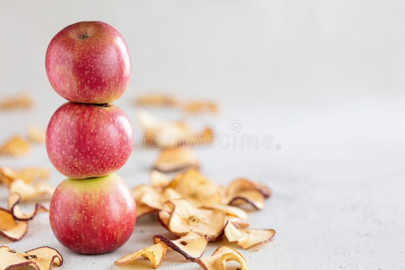 Stack of three fresh apples and Sun dried apple chips as a healthy snack royalty free stock photos