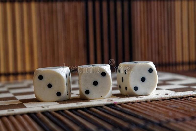 Stack of three white plastic dices on brown wooden board background. Six sides cube with black dots. Number 3 stock photography