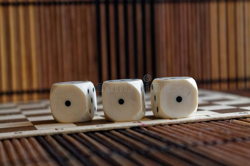 Stack of three white plastic dices on brown wooden board background. Six sides cube with black dots. Number 1 royalty free stock photography
