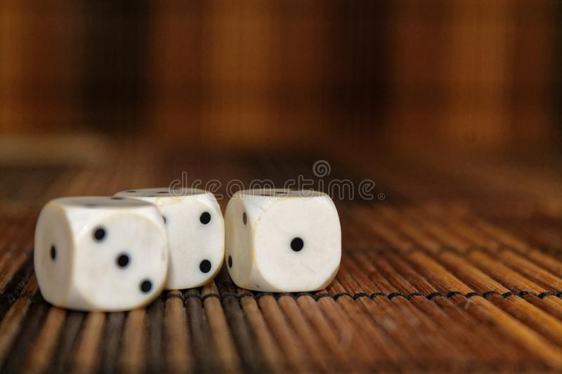 Stack of three white plastic dices on brown wooden board background. Six sides cube with black dots. Number 1, 3 royalty free stock photo