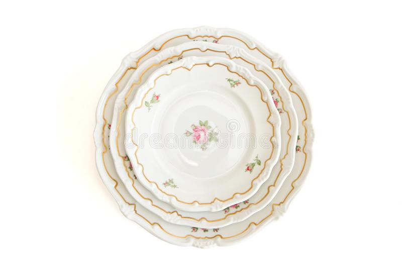 Stack of three white plates and saucers top view. Stack of three white dinner plates and saucers with flowers and wavy rim top view isolated royalty free stock image