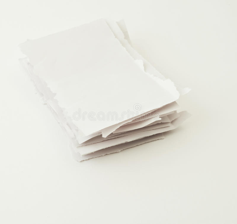 Stack of torn paper pieces over white stock photo