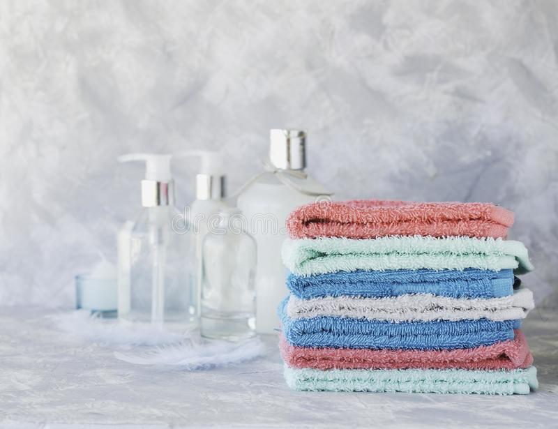 Stack of towels for bathroom bottles on a white marble background, space for text, selective focus stock image