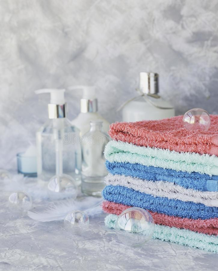 Stack of towels for bathroom bottles on a white marble background, space for text, selective focus royalty free stock photo
