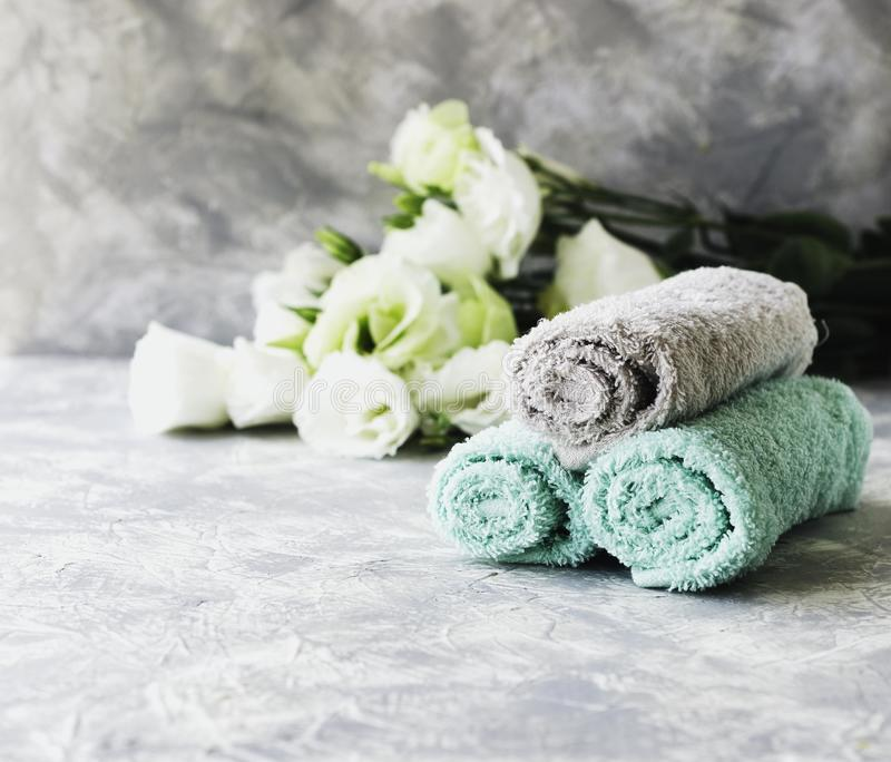 Stack of towels with flowers for spa space under the text, selective focus stock photos