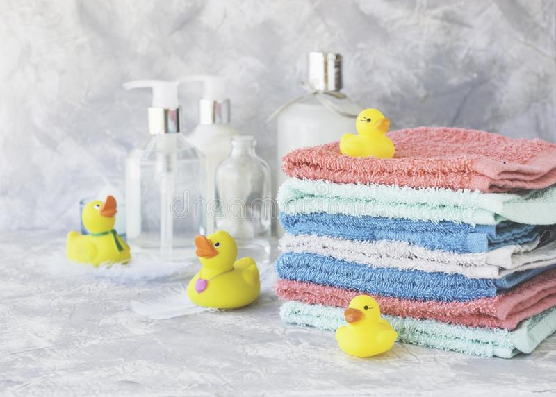 Stack of towels with yellow rubber bath ducks on white marble background, space for text, selective focus stock images