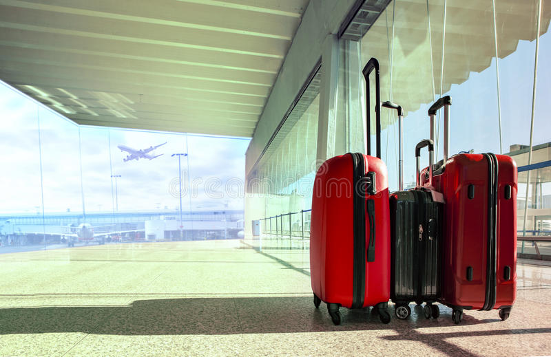 Stack of traveling luggage in airport terminal and passenger plane flying for air transport and treveling theme royalty free stock image