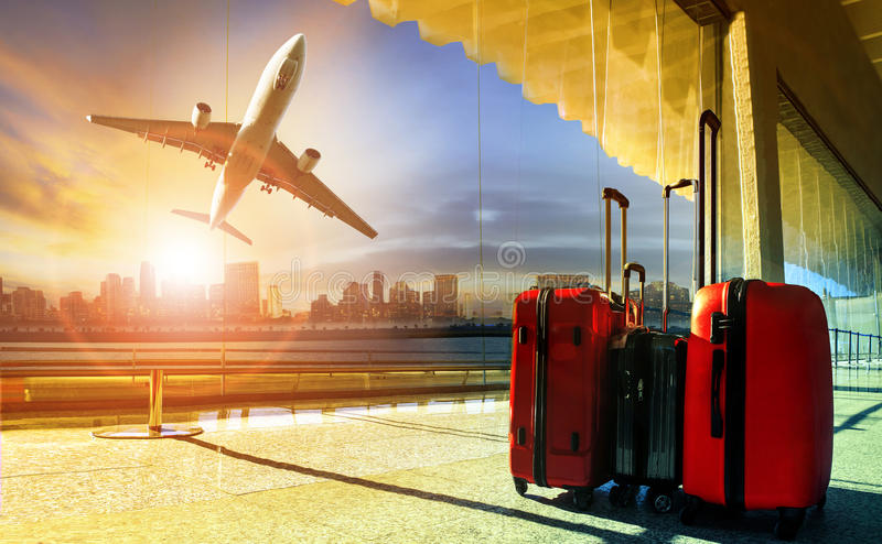 stack of traveling luggage in airport terminal and passenger plane flying over building in city royalty free stock photography