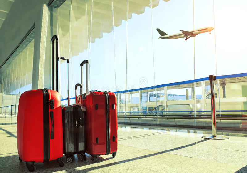 stack of traveling luggage in airport terminal and passenger plane flying over sky stock images