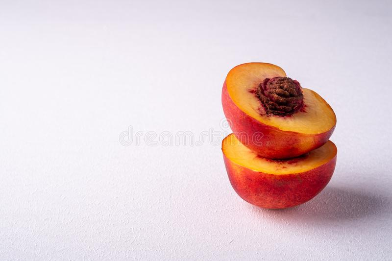 Stack of two slice of peach nectarine fruit with seed on white background, copy space, angle view. Close up royalty free stock images