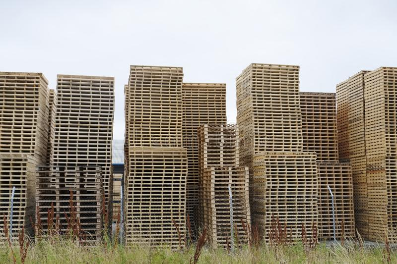 Stack of used wooden timber pallets for transportation of goods royalty free stock image