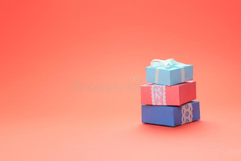 Stack of Various birthday gift boxes with lace on coral color background. Minimal concept, greeting card, mockup royalty free stock photography