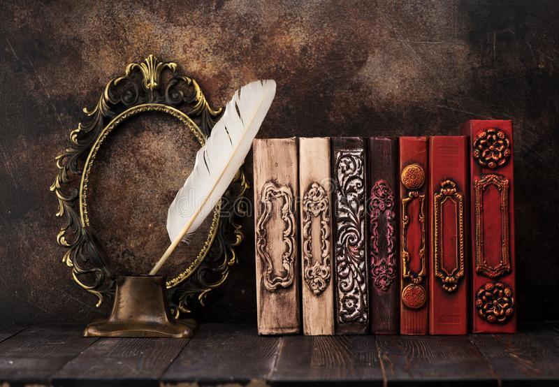 Stack vintage books on a shelf, bronze empty frame and Ancient inkwell royalty free stock photography