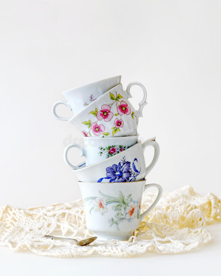 Stack of vintage tea cups. Antique tea cups stacked for high tea on a white background stock photos
