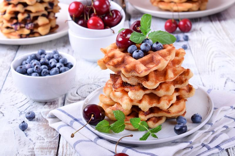 Stack of waffles topped with fresh bilberries, cherries and mint. On the white wooden table stock photo