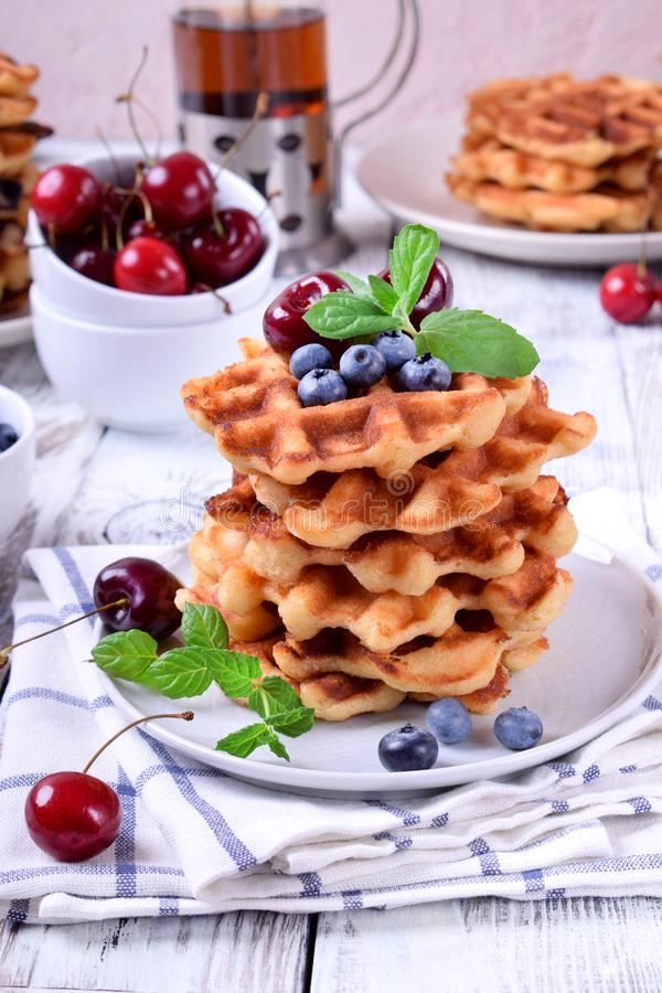 Stack of waffles topped with fresh bilberries, cherries and mint. On the white wooden table stock photos