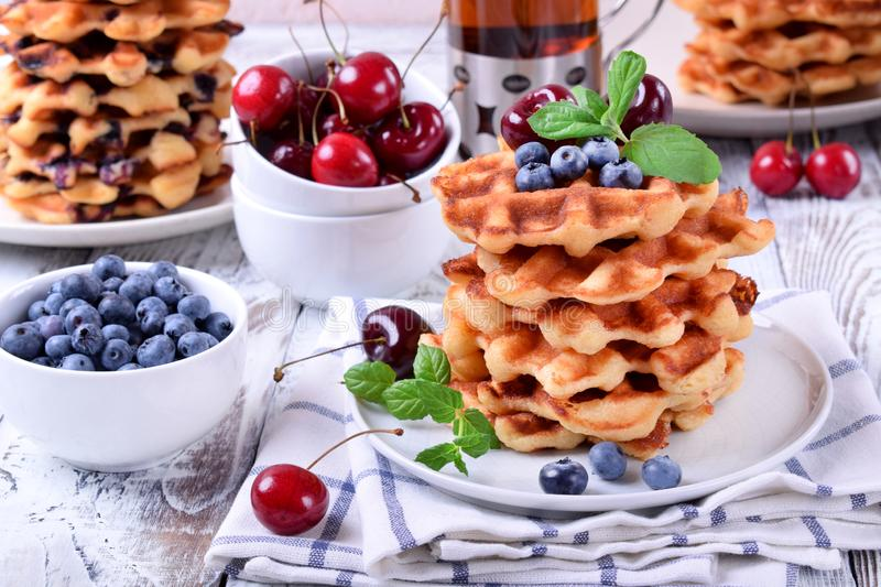Stack of waffles topped with fresh bilberries, cherries and mint. On the white wooden table royalty free stock photography