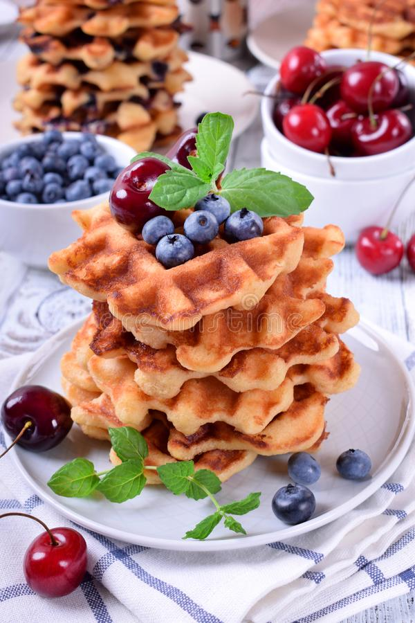 Stack of waffles topped with fresh bilberries, cherries and mint. On the white wooden table stock photography