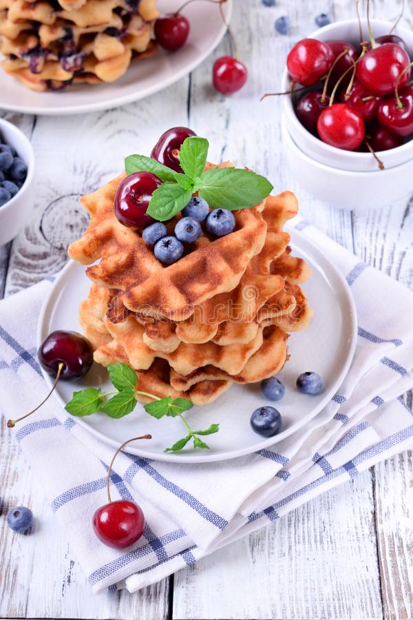 Stack of waffles topped with fresh bilberries, cherries and mint. On the white wooden table royalty free stock image