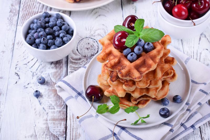 Stack of waffles topped with fresh bilberries, cherries and mint. On the white wooden table royalty free stock photo