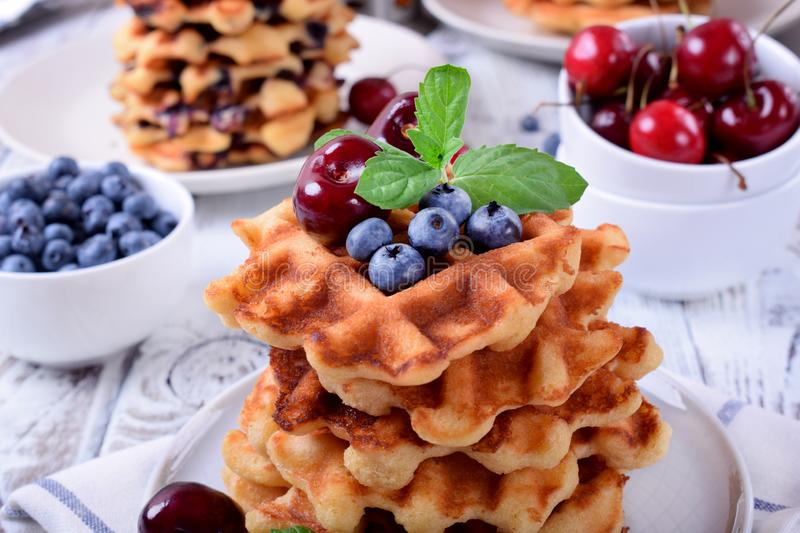 Stack of waffles topped with fresh bilberries, cherries and mint. On the white wooden table stock image