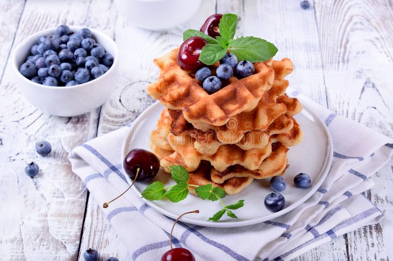 Stack of waffles topped with fresh bilberries, cherries and mint. On the white wooden table stock images
