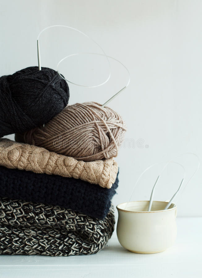 Stack of warm clothes from knitted knitwear with a cup over whit stock photos