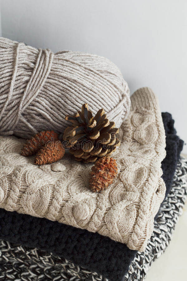 Stack Of Warm Clothes From Knitted Knitwear With Pine Cones Over ...
