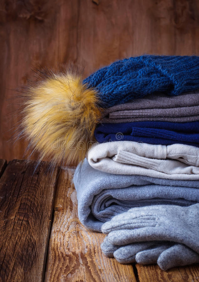 Stack of warm knitted clothes stock images