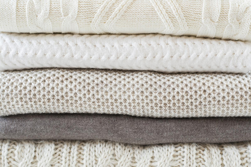 Stack of warm light sweaters. Close up stock photo