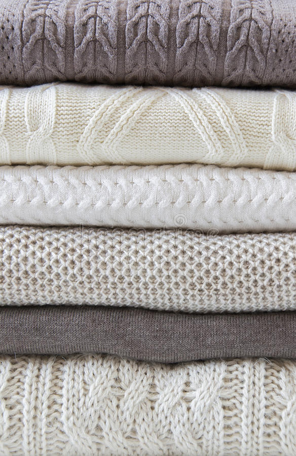 Stack of warm light sweaters. Vertical, close up royalty free stock photo