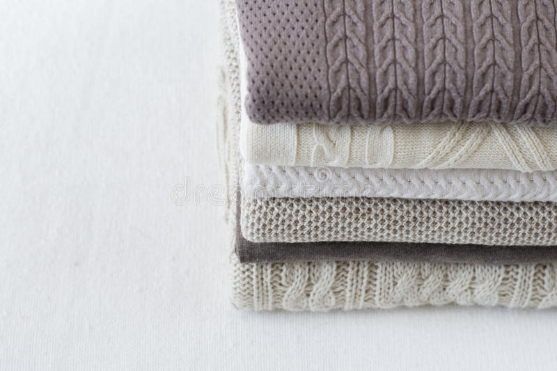 Stack of warm light sweaters. Vertical, close up stock photography