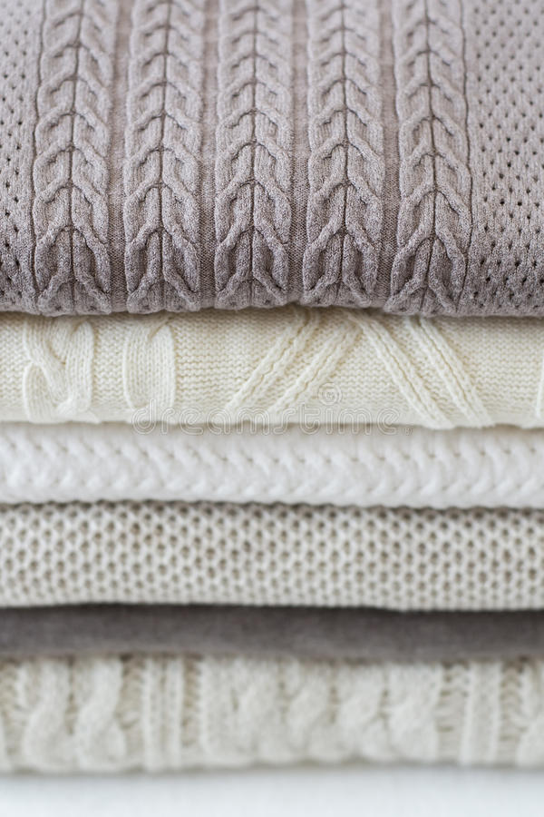 Stack of warm light sweaters. Vertical, close up stock images