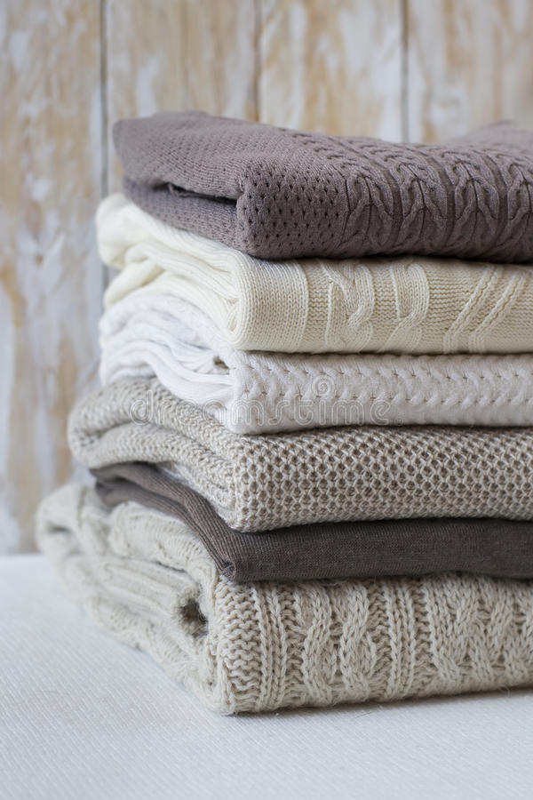 Stack of warm light sweaters. Vertical, close up stock image