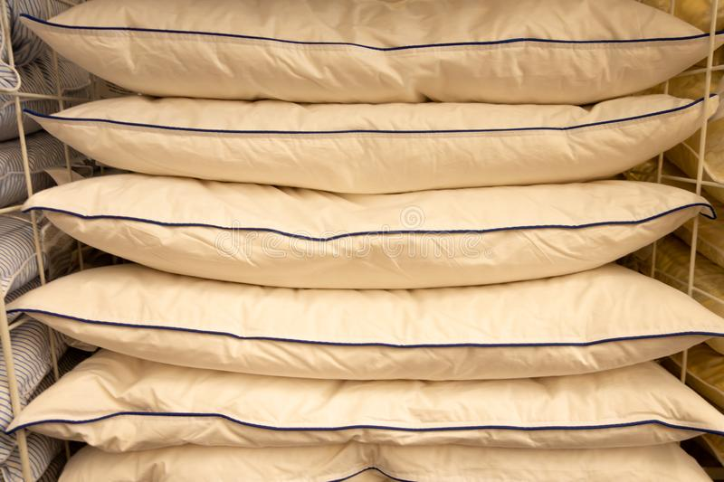 Stack of warm plaid and pillows on white shelf against striped wall background.  stock photos
