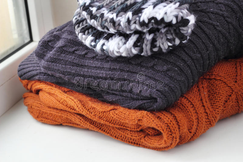 Stack of warm winter knitted sweaters royalty free stock photo