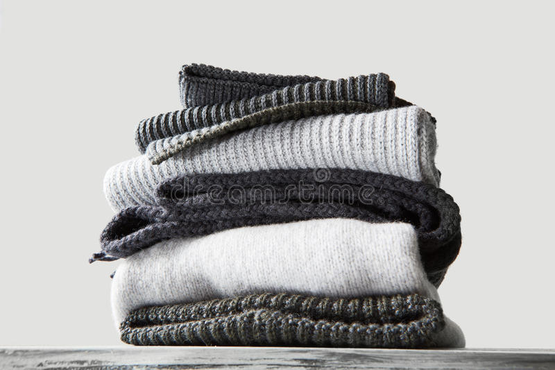 Stack of warm winter knitted sweaters stock images