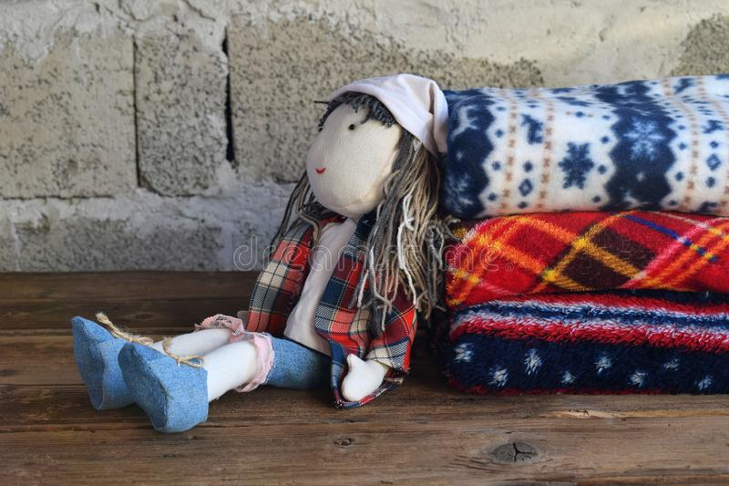Stack of warm woolen blankets and doll on wooden background. Childrens textile toys. Home cosiness. Handmade toy. Colorful plaids royalty free stock images