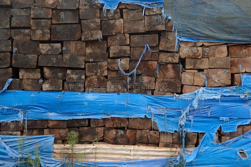 Stack of weathered wooden railroad cross ties covered by blue torn plastic royalty free stock photos