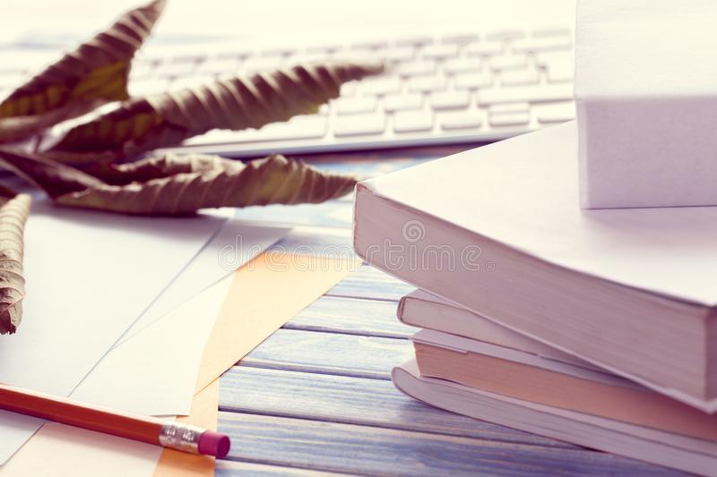 Stack of white books with pencil and keyboard stock images