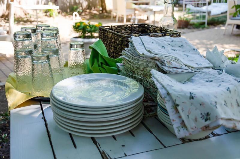 A stack of white clean plates, glasses, colored napkins on a wooden table. Preparing for guest service in the restaurant. A stack of white clean plates, glasses royalty free stock image
